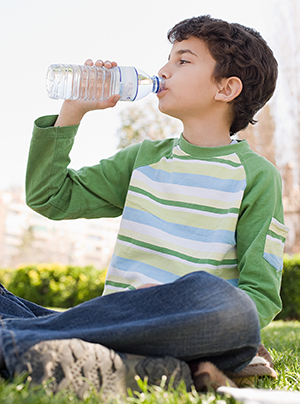 Boy drinking water from bottle sitting on grass outdoors.